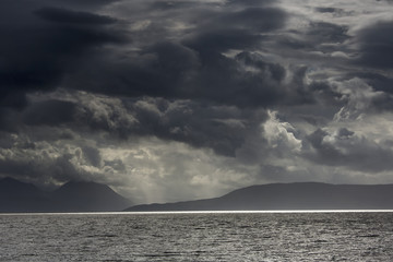 Dramatic sky with dark storm clouds over the ocean and a view of a silhouette of the coastline;Applecross peninsula scotland