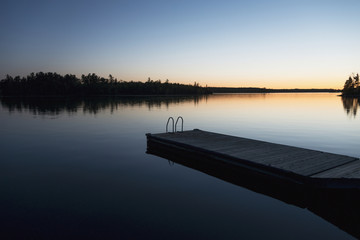 Sunset over a lake with a wooden dock;Lake of the woods ontario canada