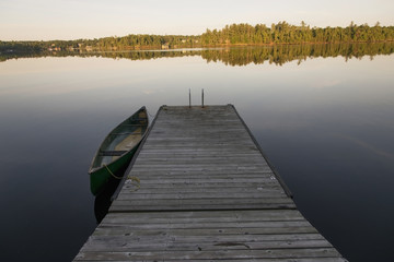 A canoe tied to a wooden dock on a tranquil lake;Ontario canada