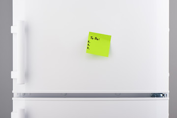 To do list on green note paper on white refrigerator