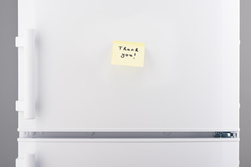 Thank you note on yellow sticky paper on white refrigerator