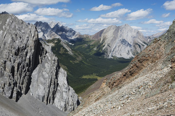 Looking down a mountain pass with valley and mountains in the distance with blue sky and clouds;Alberta canada