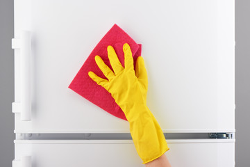 Hand in yellow glove cleaning refrigerator with pink rag