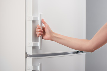 Female hand holding handle of white refrigerator door