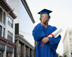A graduate in cap and gown holds his hand over his eyes;Victoria british columbia canada