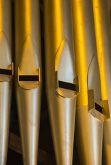 Close up of the gold pipes of a pipe organ; Northumberland, England