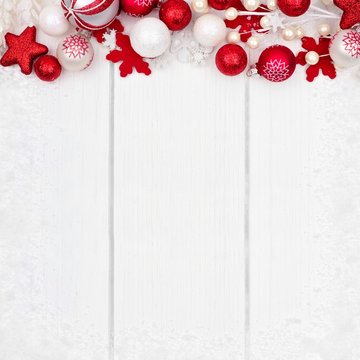 Red and white Christmas ornament top border with snow frame on a white wood background