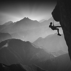 Climber on a cliff against misty mountains. Monochrome