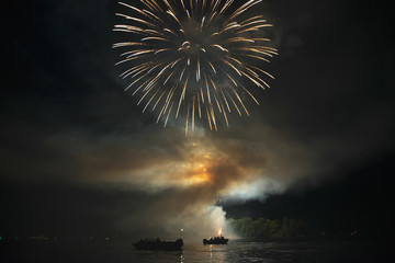Fireworks display over a lake illuminating the boats on the water; Kenora, Ontario, Canada