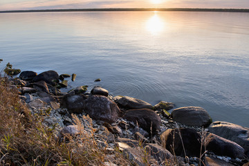 The setting sun reflects on the tranquil water with rocks along the shoreline; Riverton, Manitoba, Canada