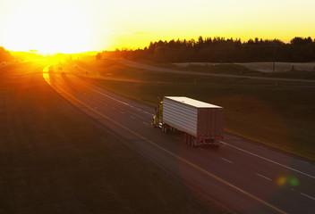 Truck heading down a highway at sunset; Edmonton, Alberta, Canada