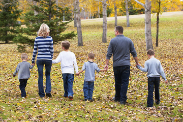 A family with four sons walking and holding hands in a park in autumn; Edmonton, Alberta, Canada