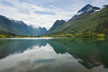 Mountains and sky reflected in the tranquil water surrounded by mountains; Olden, Norway
