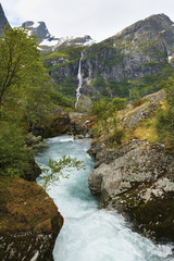 Water rushing in a river in a valley between the mountains with a waterfall on a steep cliff in the distance; Olden, Norway