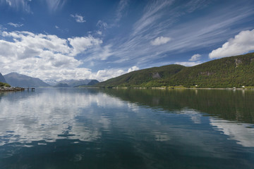 Blue sky and cloud reflected in tranquil water with forested mountains along the shoreline; Andalsnes, Rauma, Norway