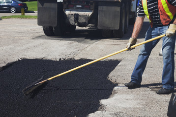 Work crew repairing pot holes in a parking lot; Edmonton, Alberta, Canada