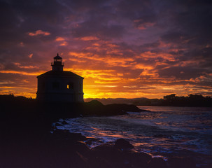 The sun rises behind the Coquille River Lighthouse; Bandon, Oregon, United States of America