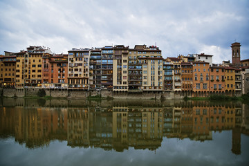 Colourful residential buildings along the shoreline reflected in the water; Florence, Tuscany, Italy