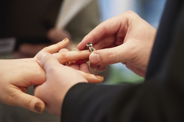 A groom puts a ring on the bride's finger; Edmonton, Alberta, Canada