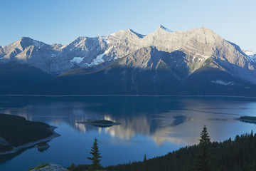 Mountain Range Reflecting In A Lake At Sunrise With Blue Sky; Kananaskis Country, Alberta, Canada