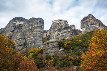 Monastery perched on a cliff with autumn foliage; Meteora, Greece