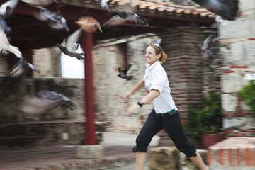 A young woman runs after a flock of birds taking flight; Cartagena, Columbia