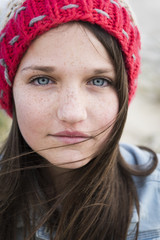 Portrait of a young woman with freckles, blue eyes and long brown hair; Tarifa, Cadiz, Andalusia, Spain