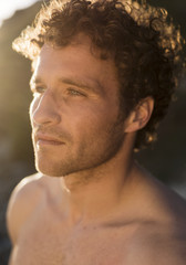 Portrait of a shirtless man with curly hair; Tarifa, Cadiz, Andalusia, Spain