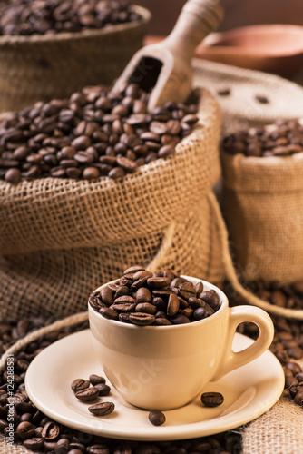 """Popolare chicchi di caffè tostato in tazzina e sacchi di iuta"""" Immagini e  RN05"""