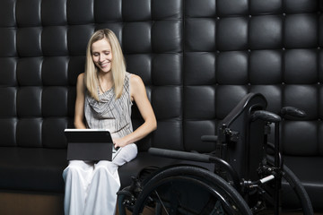 Young professional business woman who is a paraplegic working on her computer; St. Albert, Alberta, Canada