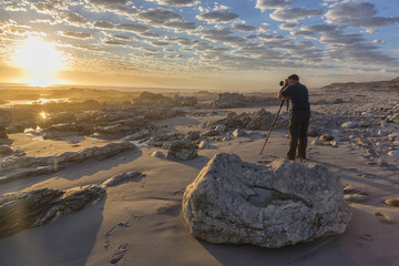 Man photographing sunset at Marble Beach, South Africa