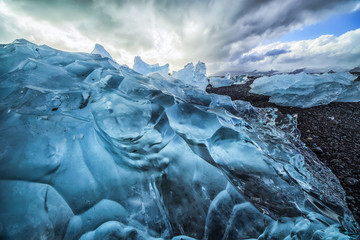 Along the south shore of Iceland, large chunks of ice litter the beach after being washed out to sea from the Jokulsarlon lagoon; Iceland