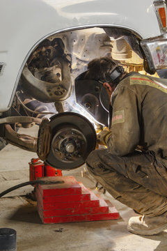 A welder wearing coveralls and his protective face shield is at work on a truck axle with a welding gun; Port McNeill, British Columbia, Canada