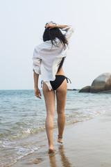 Young woman walking on the beach in a bikini; Xiamen, China