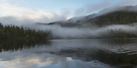 Tranquil water reflecting the coastline and clouds with fog hanging low over the water; Skeena-Queen Charlotte, British Columbia, Canada