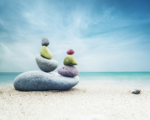 Photo sur Plexiglas Zen pierres a sable Balancing colorful zen stones pyramid on sandy beach under blue sky. Beautiful nature and spiritual concept