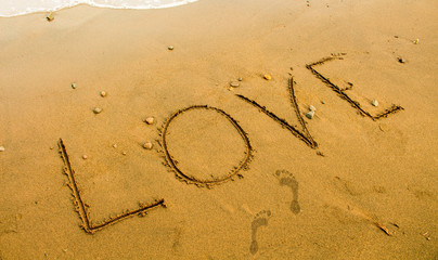 Beach sand writing. Romantic seaside photo background or card template.