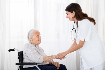 Female Doctor Consoling Disabled Senior Patient