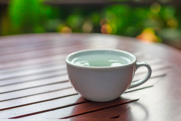 tea cup with hot water on table cloth