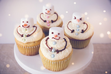 Fun homemade melting snowman cupcakes for kids, toning background