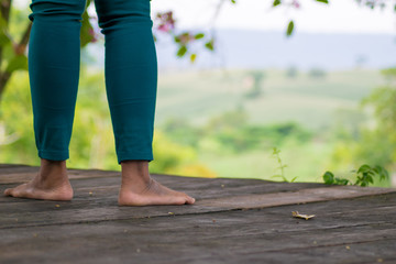 leg woman on wooden floor with moutain background