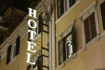 Hotel glowing sign on old facade at night. Europe