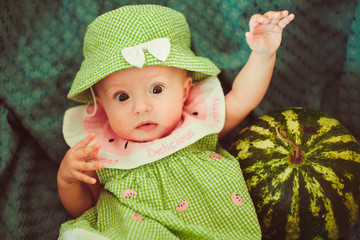 little newborn girl  holding a large watermelon