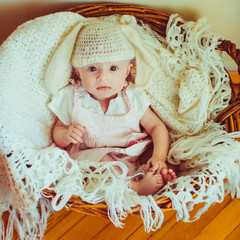 lovely girl in a nice hat sitting in a wooden basket