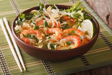 Laksa soup with shrimps, noodles, sprouts and coriander in a bowl close-up. Horizontal