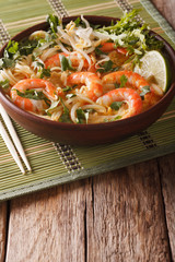 Laksa soup with shrimps, noodles, sprouts and coriander in a bowl close-up. vertical