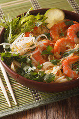 Asian food: soup with shrimps, noodles and herbs close up in a bowl. vertical