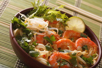 Thick soup with shrimps, noodles and herbs close up in a bowl. horizontal