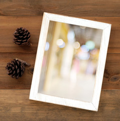 Blur bokeh on white wooden frame and pine cones on wood backgrou