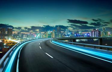 Blue neon light highway overpass motion blur with city  skyline background , night scene .